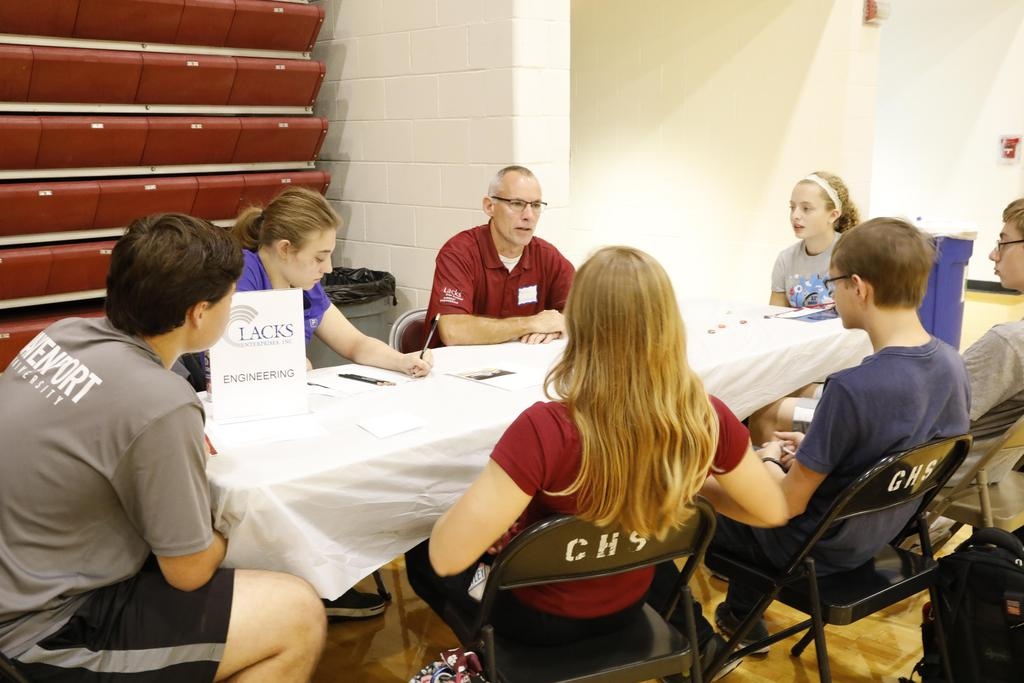 professional speaking to students at table
