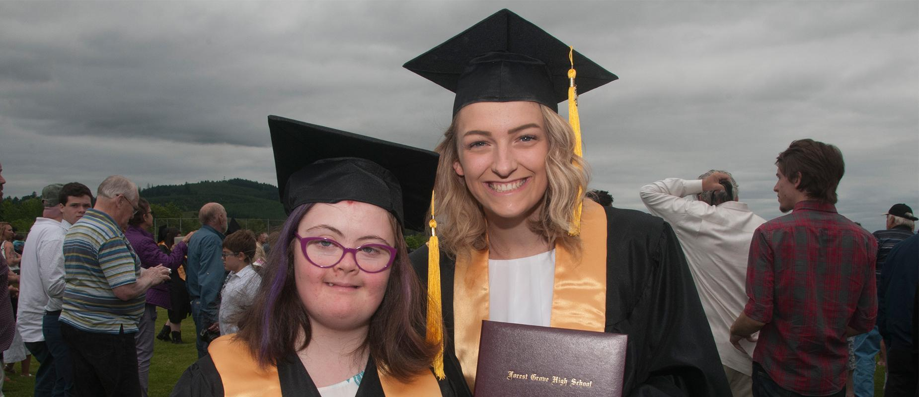Two graduates posing for picture in cap and gown