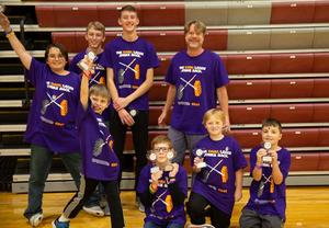 elementary lego league team holding trophy