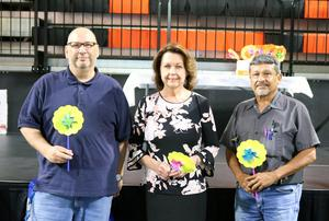 Three people holding pinwheels