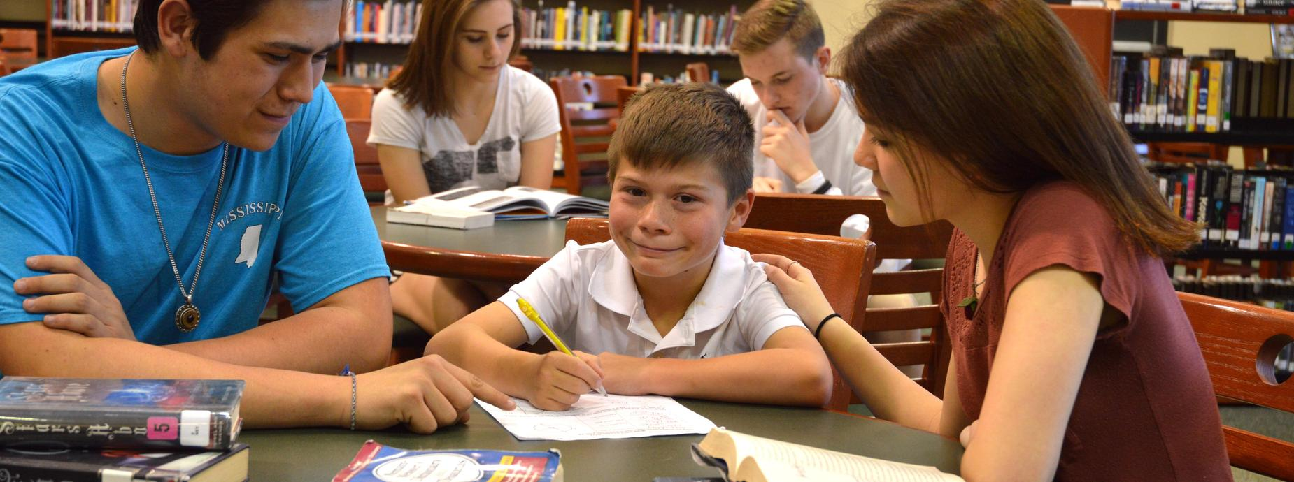 High School students helping elementary student with homework