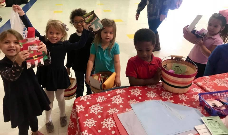 students showing the items they purchased at our Santa Store