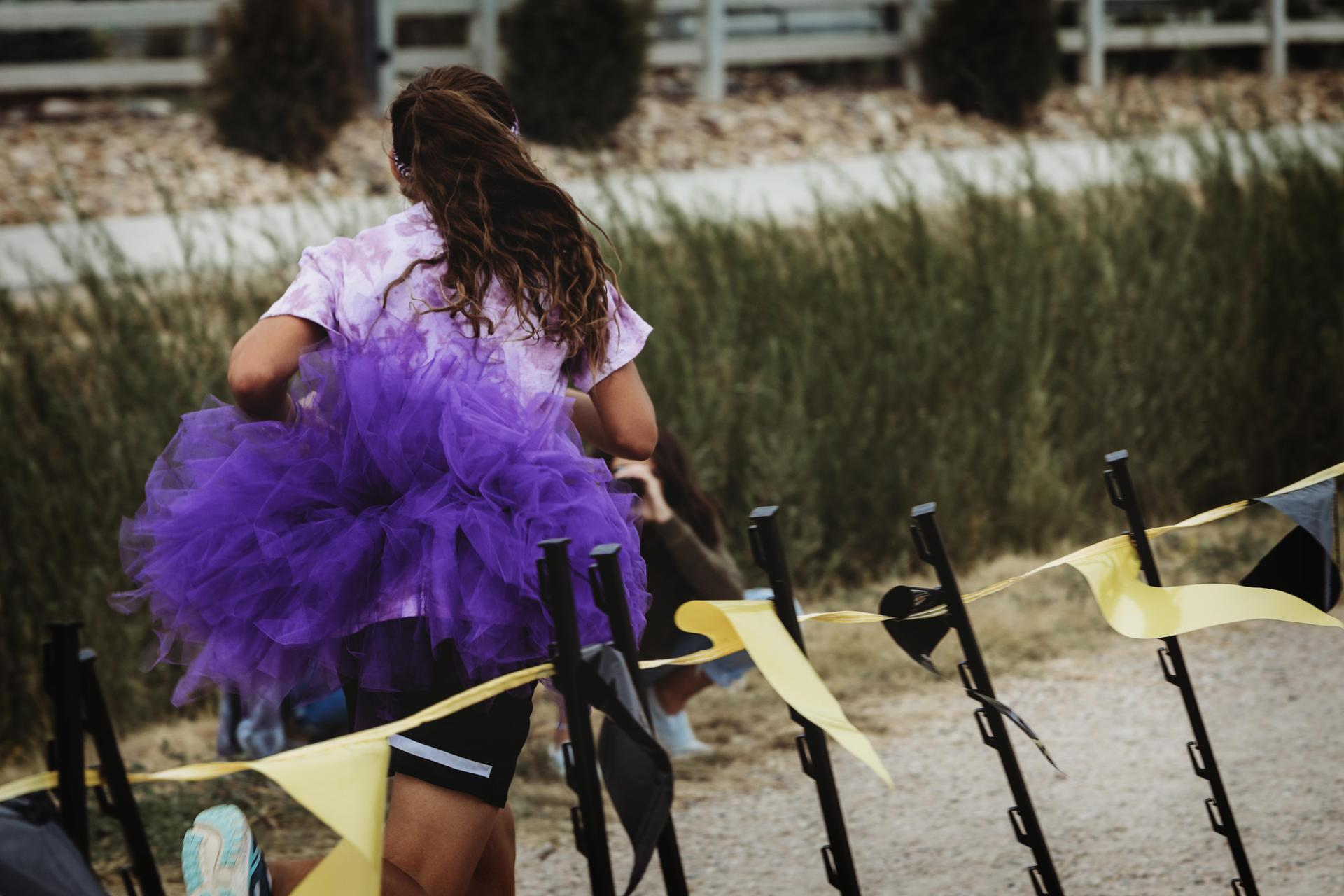Girl in purple tute running to finish line