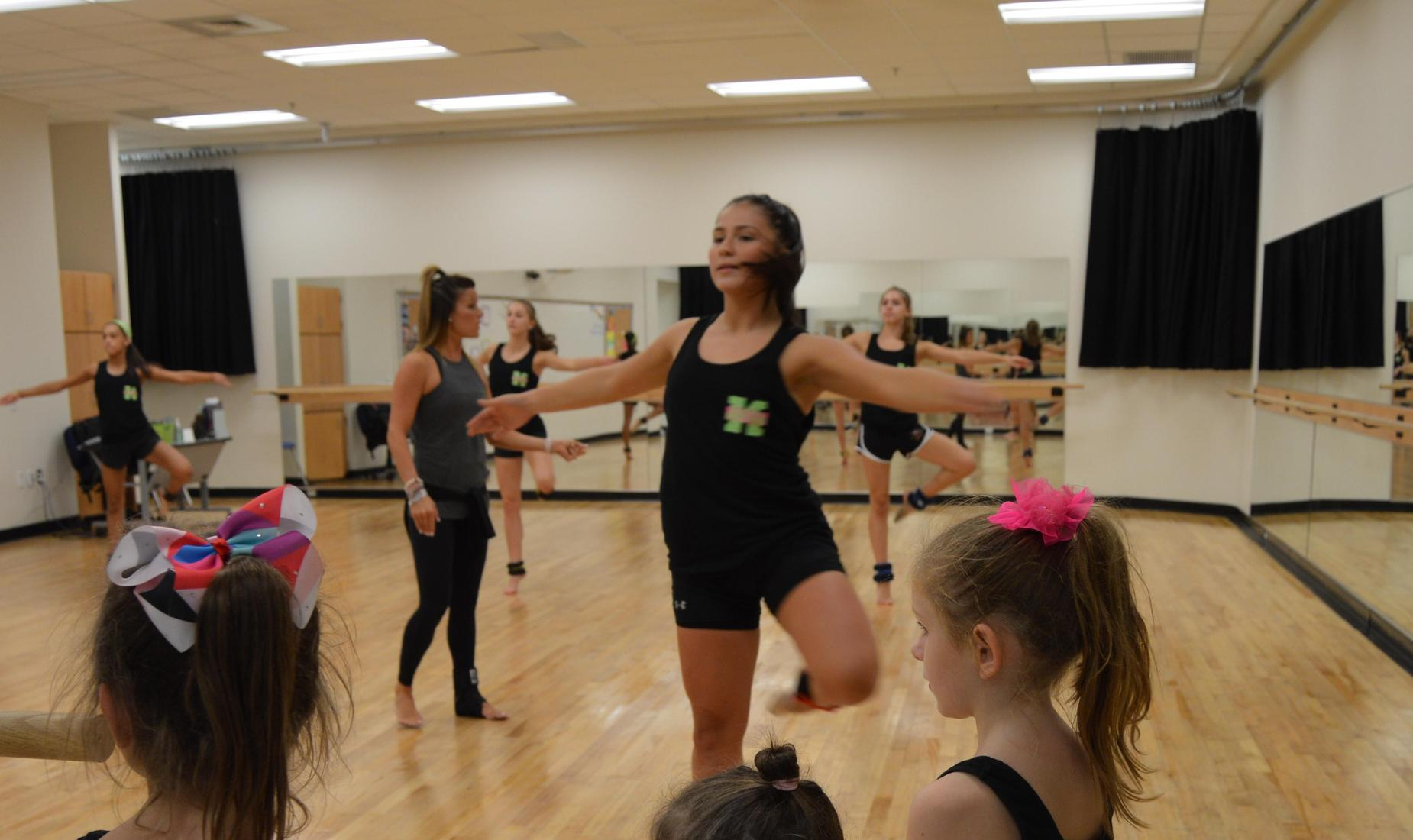 4 dancers and their instructor in the Bensalem High School Dance Studio doing twirls as 3 young students watch