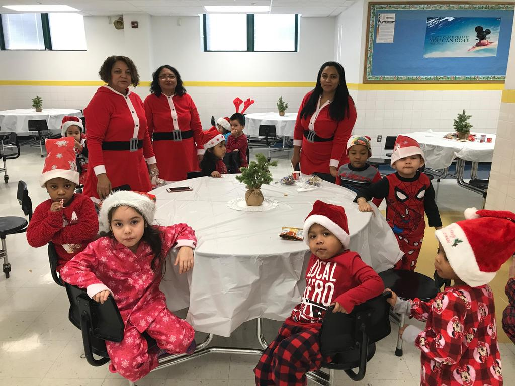 teachers aides dressed as santas helpers with the children waiting for santa