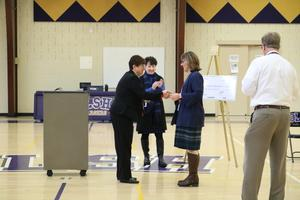 photo of teacher receiving a congratulatory handshake from another woman
