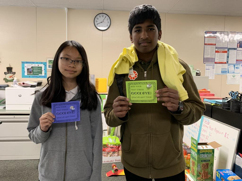 Two students standing and holding inspirational messages.