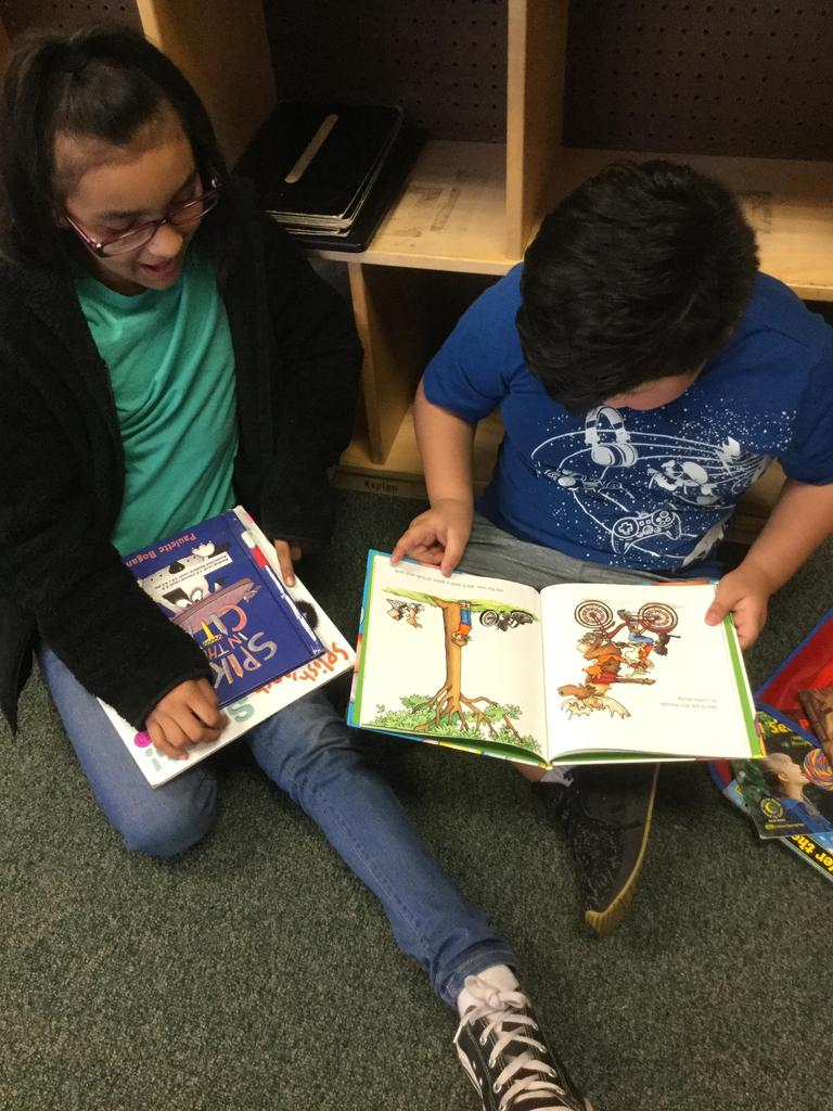 kindergarten student reads his book to third grade student