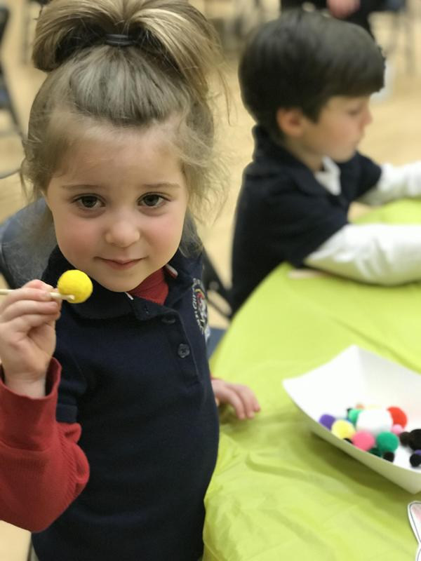 little girl showing her chopstick skills holding a yellow pom pom