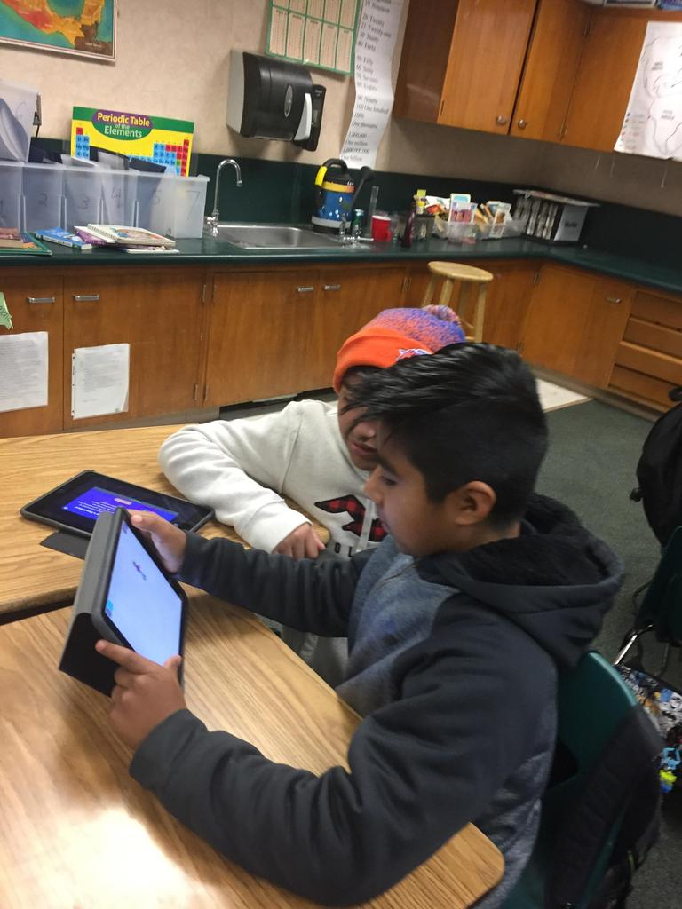 two students coding on iPad