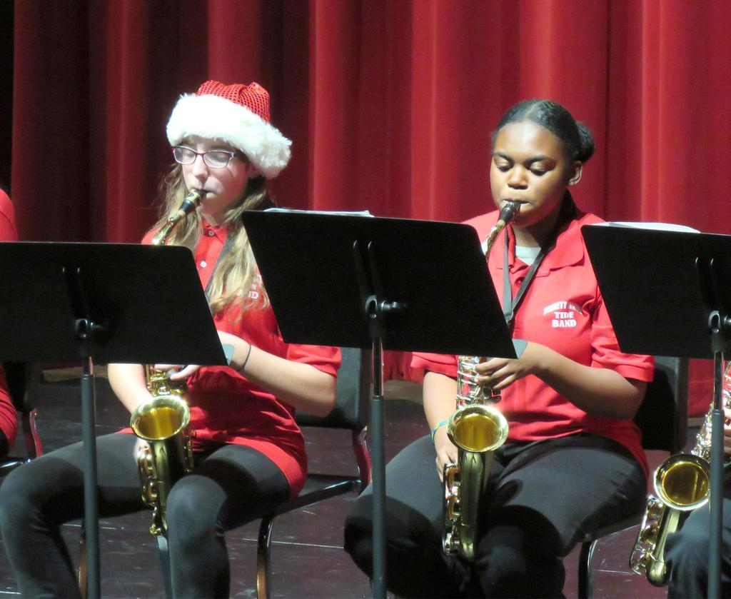 Two female saxophone players, one wearing a Santa hat, side by side on stage,