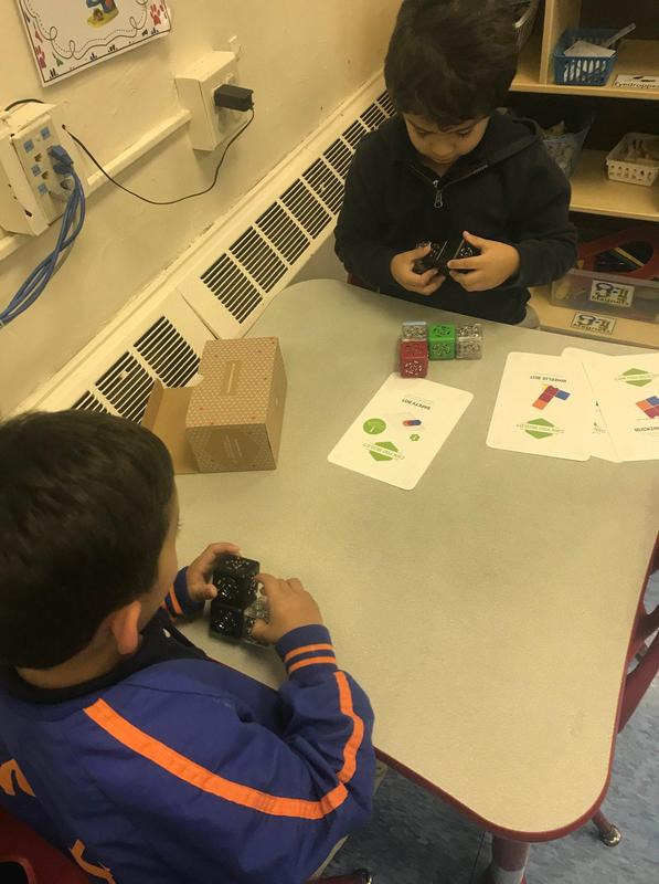 two little boys seated at a table each working with little cubes that they are putting together