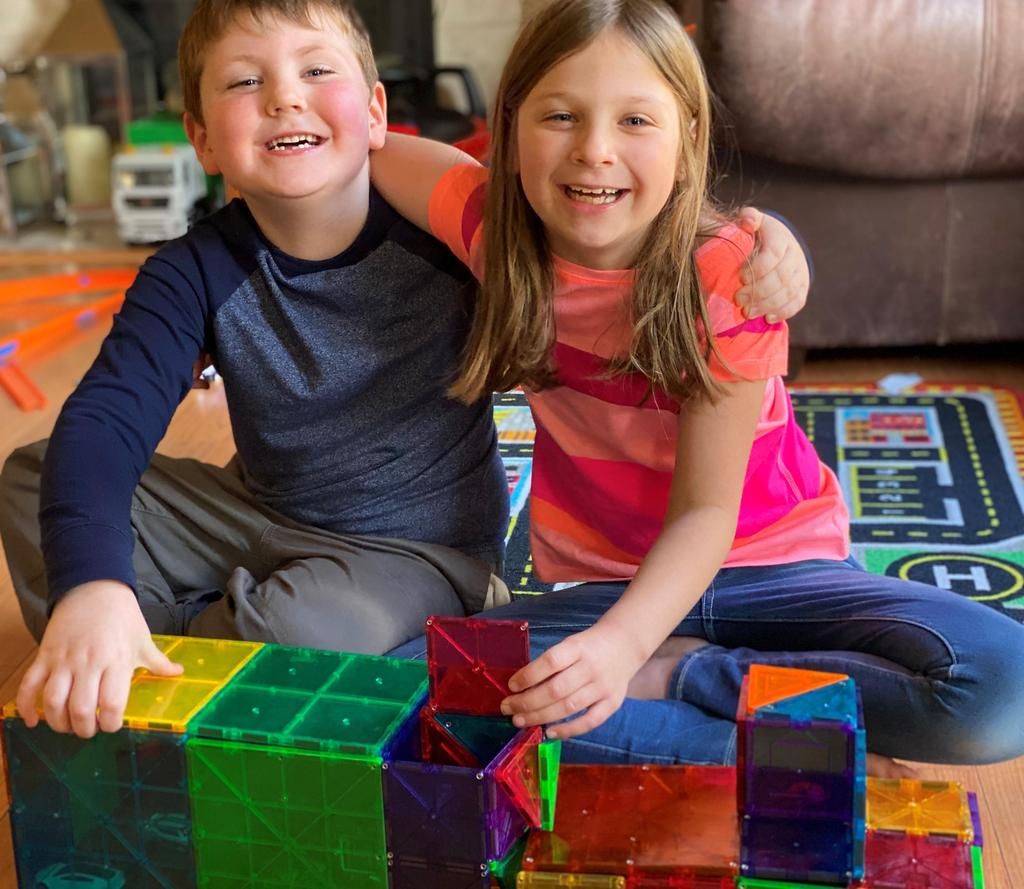 picture of boy and girl with structure of house they built out of plastic magnet squares