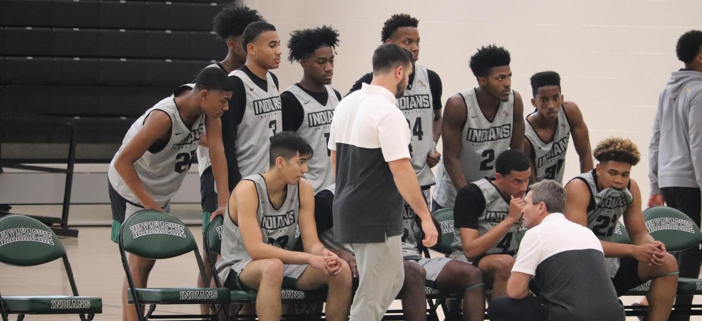 basketball coach speaking with the team beside the court