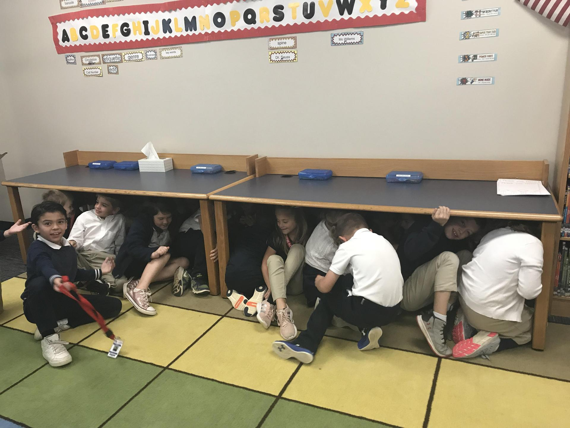 Second graders squeeze under library tables pretending they are squished on the Mayflower.