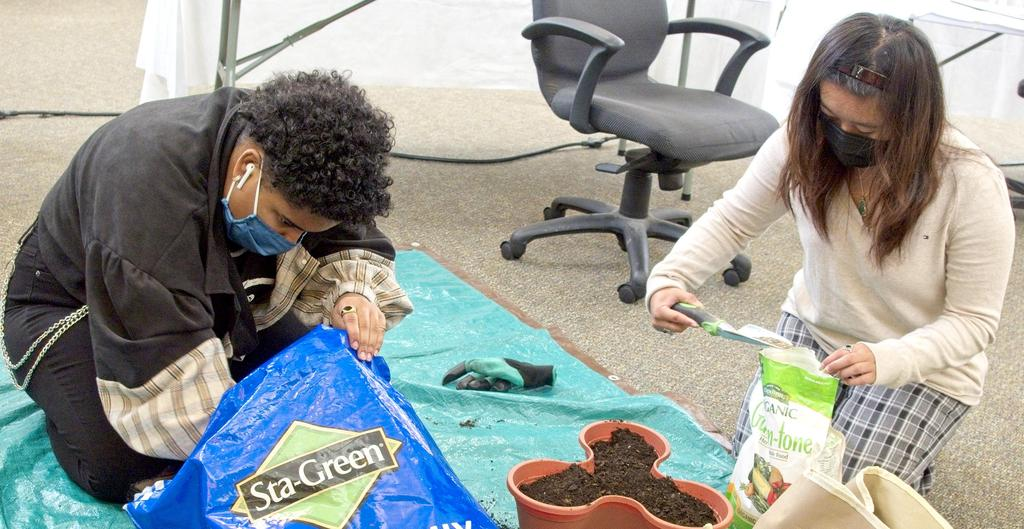 Two students working with soil and gardening supplies