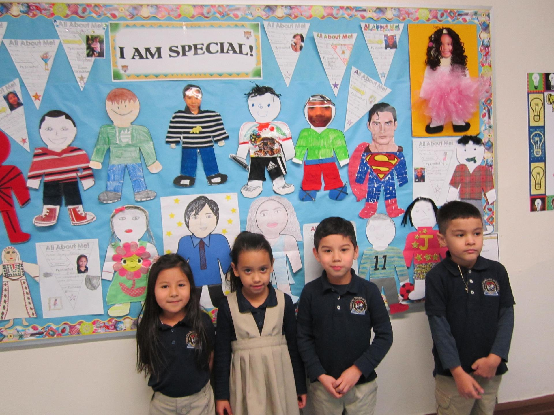 four kids showing off the bulletin board they created