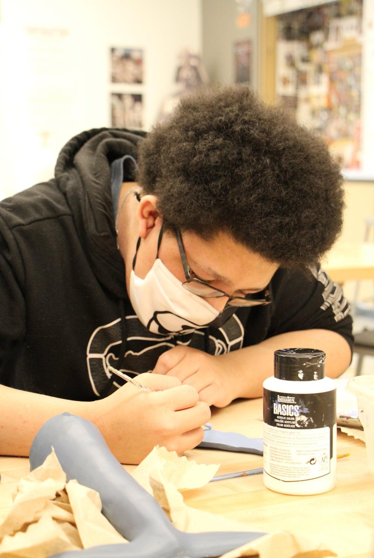 Boy painting in pottery class