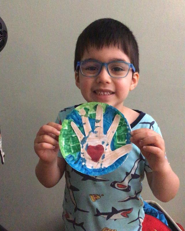 Boy holding up Earth and hand project