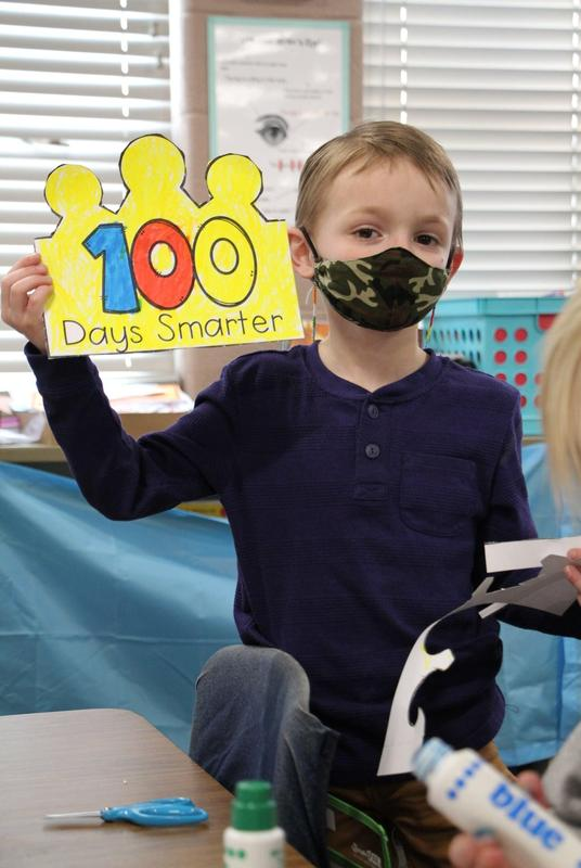 Boy holding sign in classroom