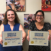 2 district office employees holding certificates of appreciation from the United Way.