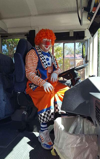 Bus Driver wearing a clown costume sitting on bus