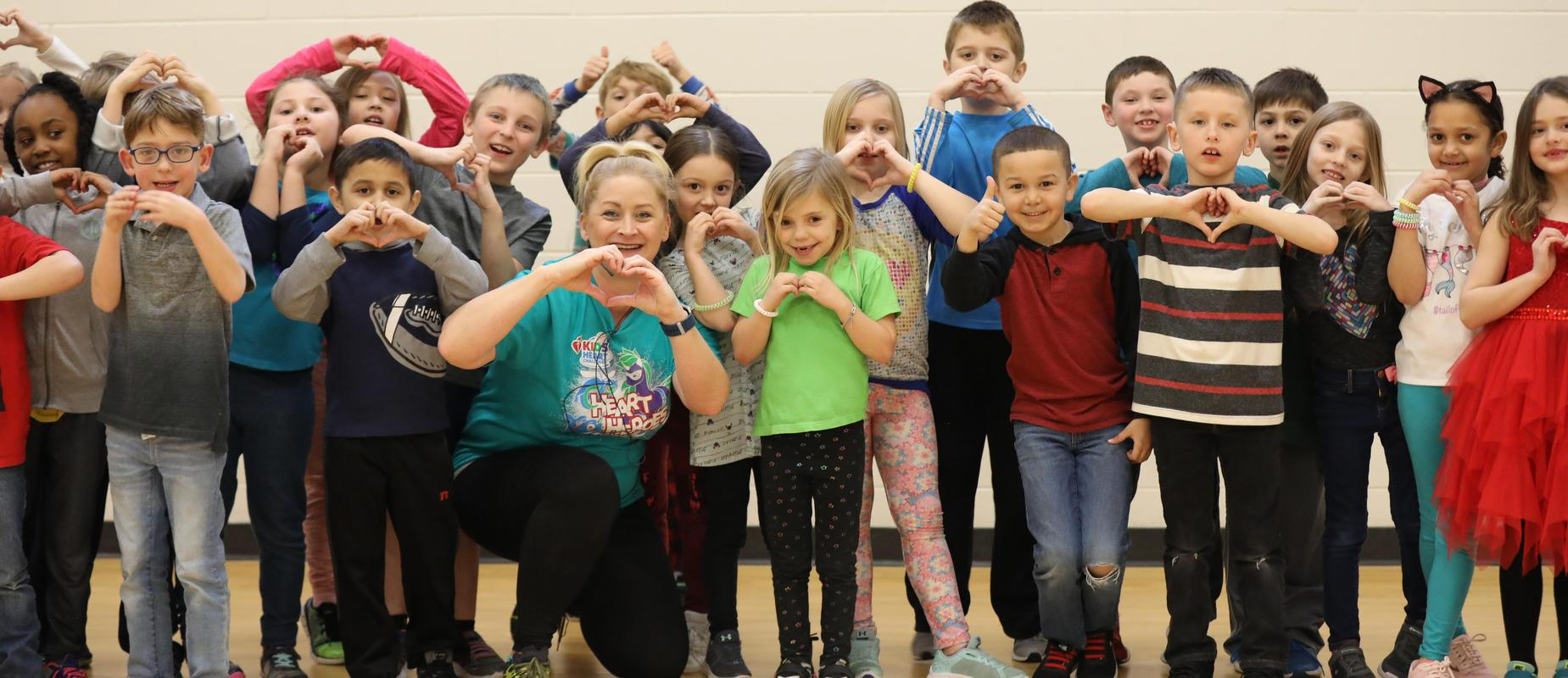first graders and gym teacher pose with their hands in the shape of a heart