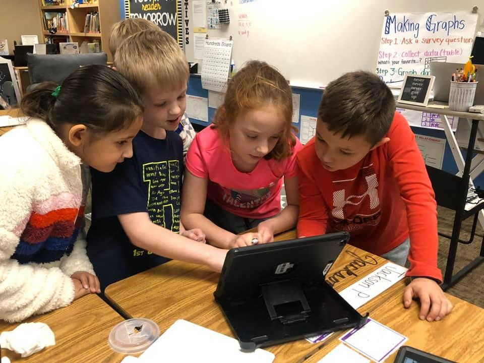 Second graders in McKenna Slater's class use their iPads and class Smartboard while they work in groups to solve a series of math problems.