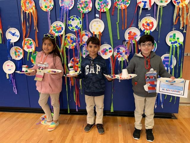 three kids showing off their finished products of puppets and kites