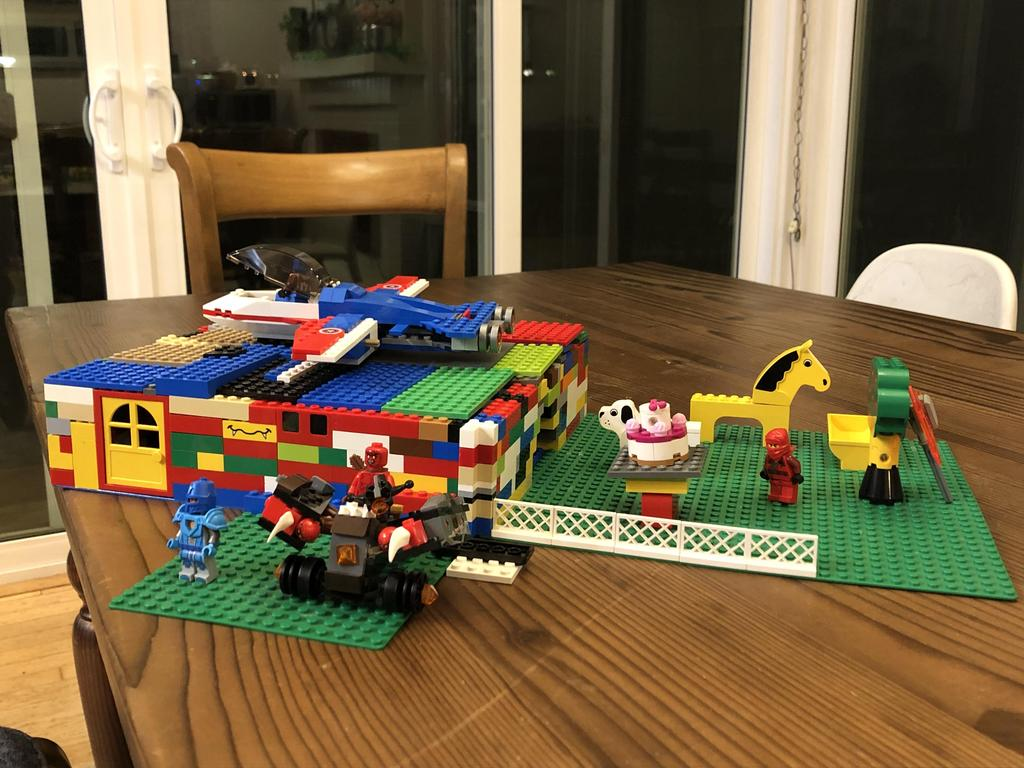 lego house with lego airplane on top and horse in yard