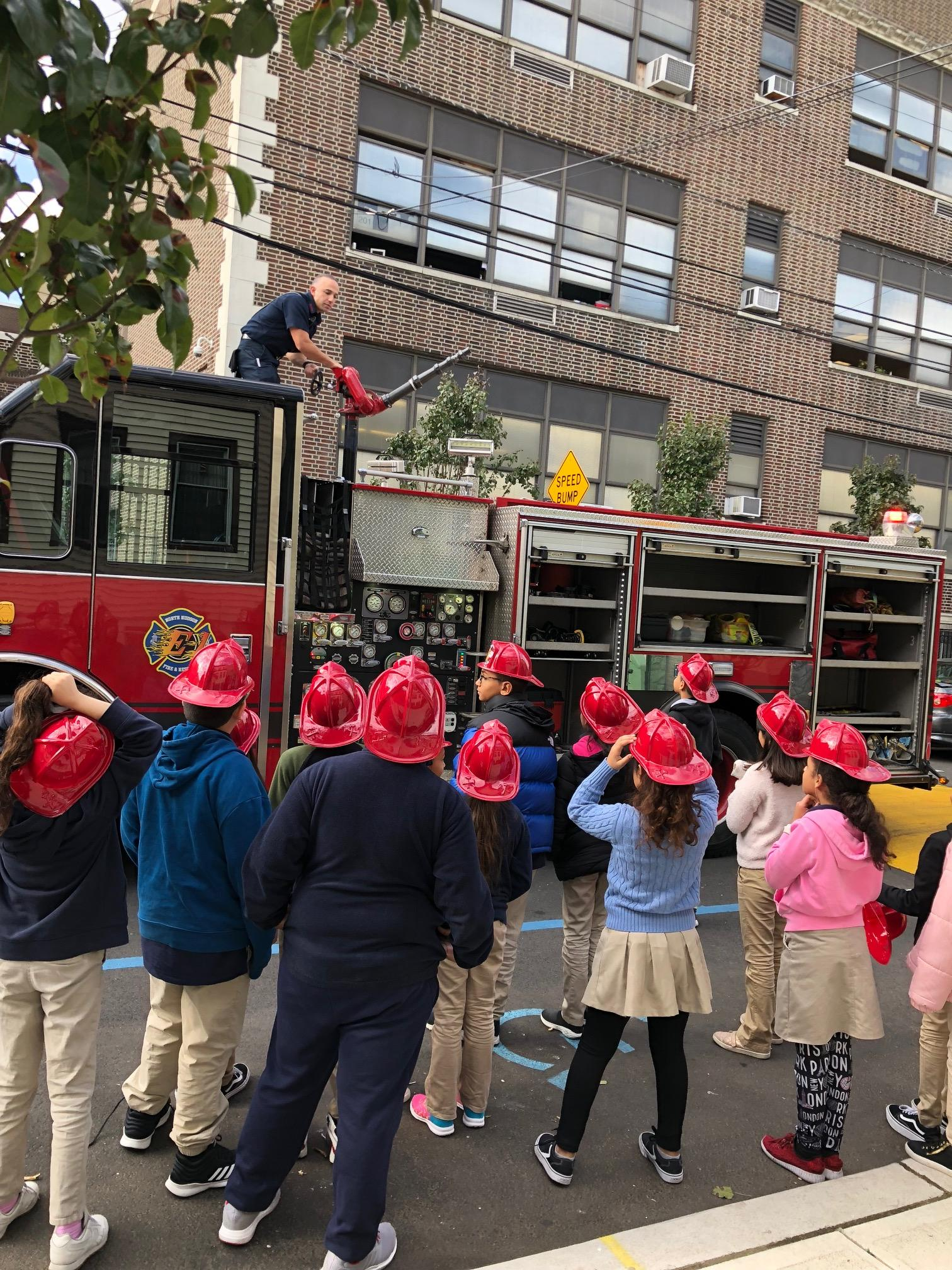 fireman showing the children the firehose on the top of the fire engine