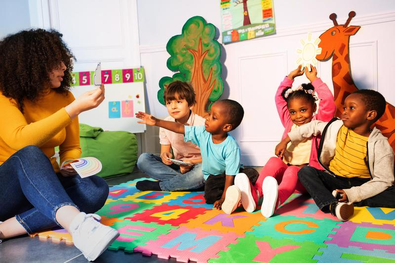 Kindergarten students sit and interact with teacher