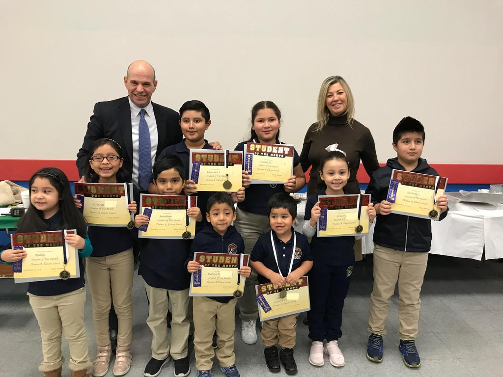 Students of the month proudly holding their certificates, ribbons, and medals with Principal Aleman and Supervisor Callabrese