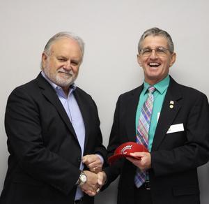 Superintendent Dr. Leland Moore presents Wtzel with a Trojan baseball cap