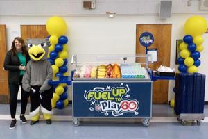 Salk School Principal and Mascot are posing next to the breakfast cart
