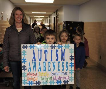 Student carrying sign he created for Autism Awareness