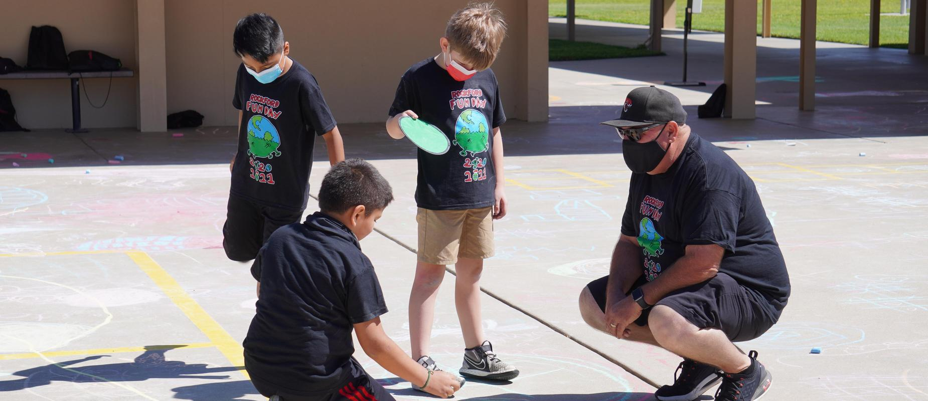 Photo of teacher and students playing with sidewalk chalk.