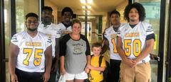Football players with boy and his mom