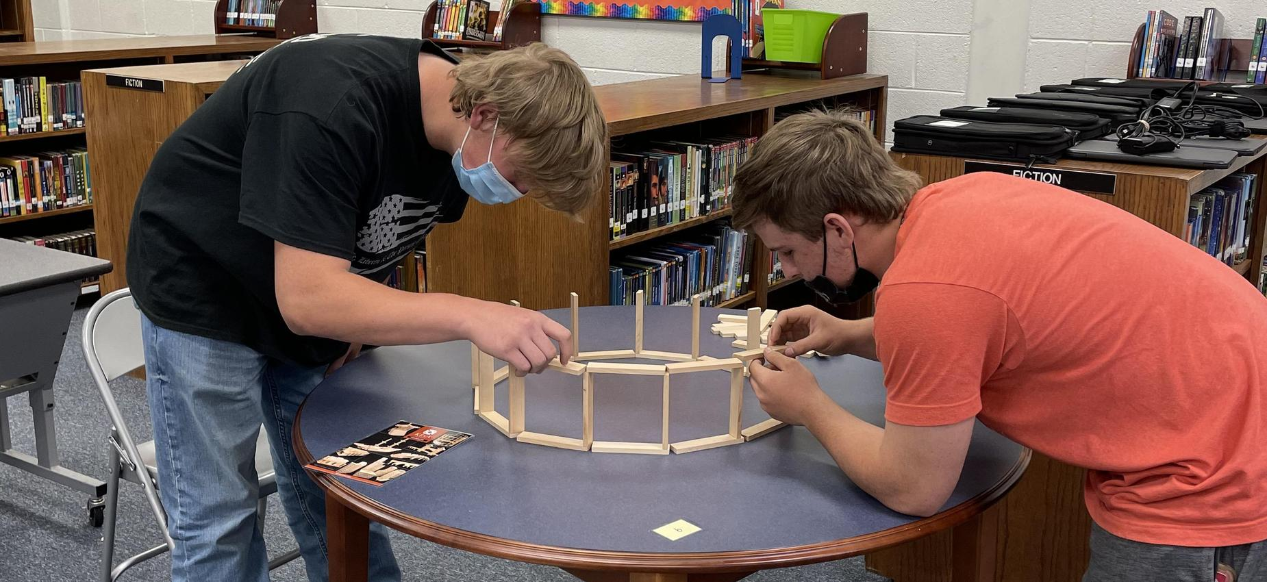 Two students work with blocks in a library.