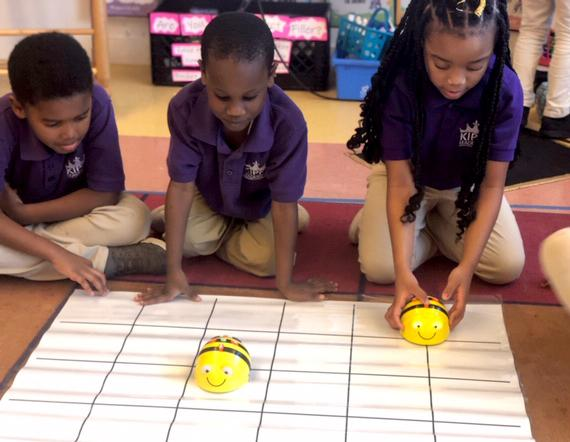 Three KLP students prepare to test their Bee Bots