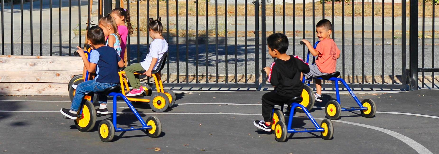 Students racing around on tricycles