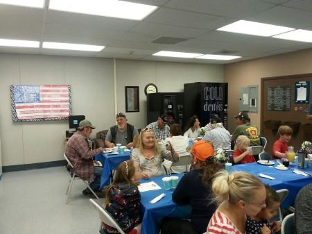 Veterans enjoying breakfast with American Flag in the background