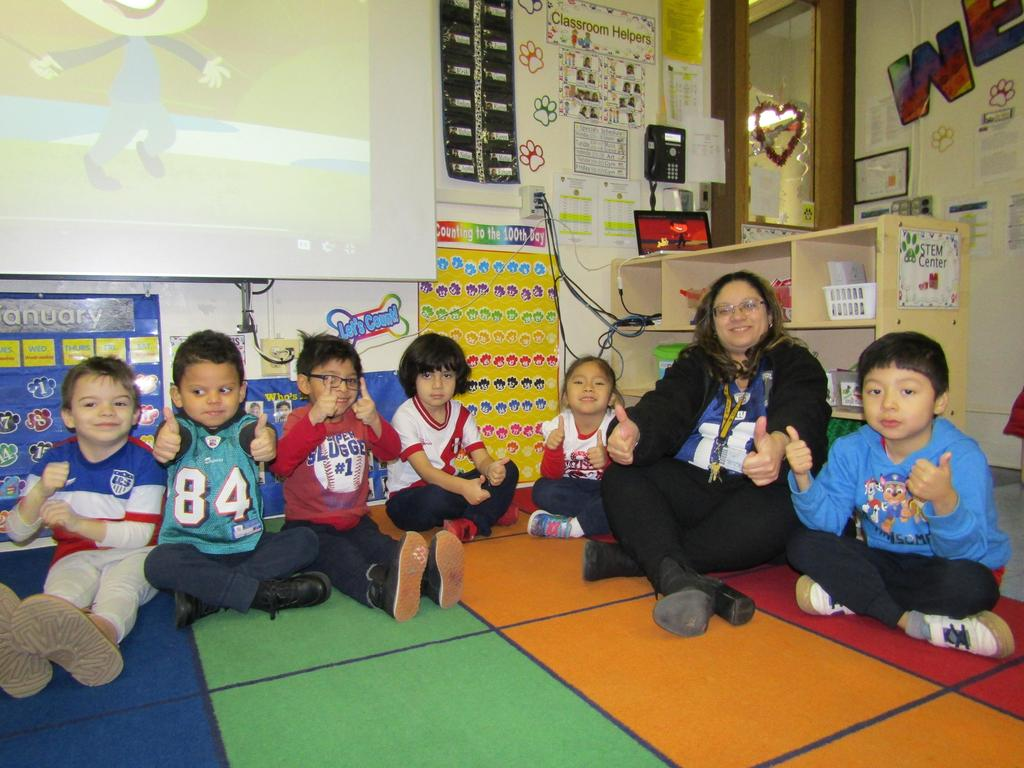 Mrs. ortiz with her prek class with thumbs up