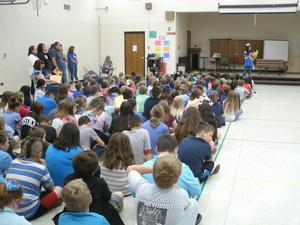 Students wearing blue in multi-purpose room for anti-bullying presentation.