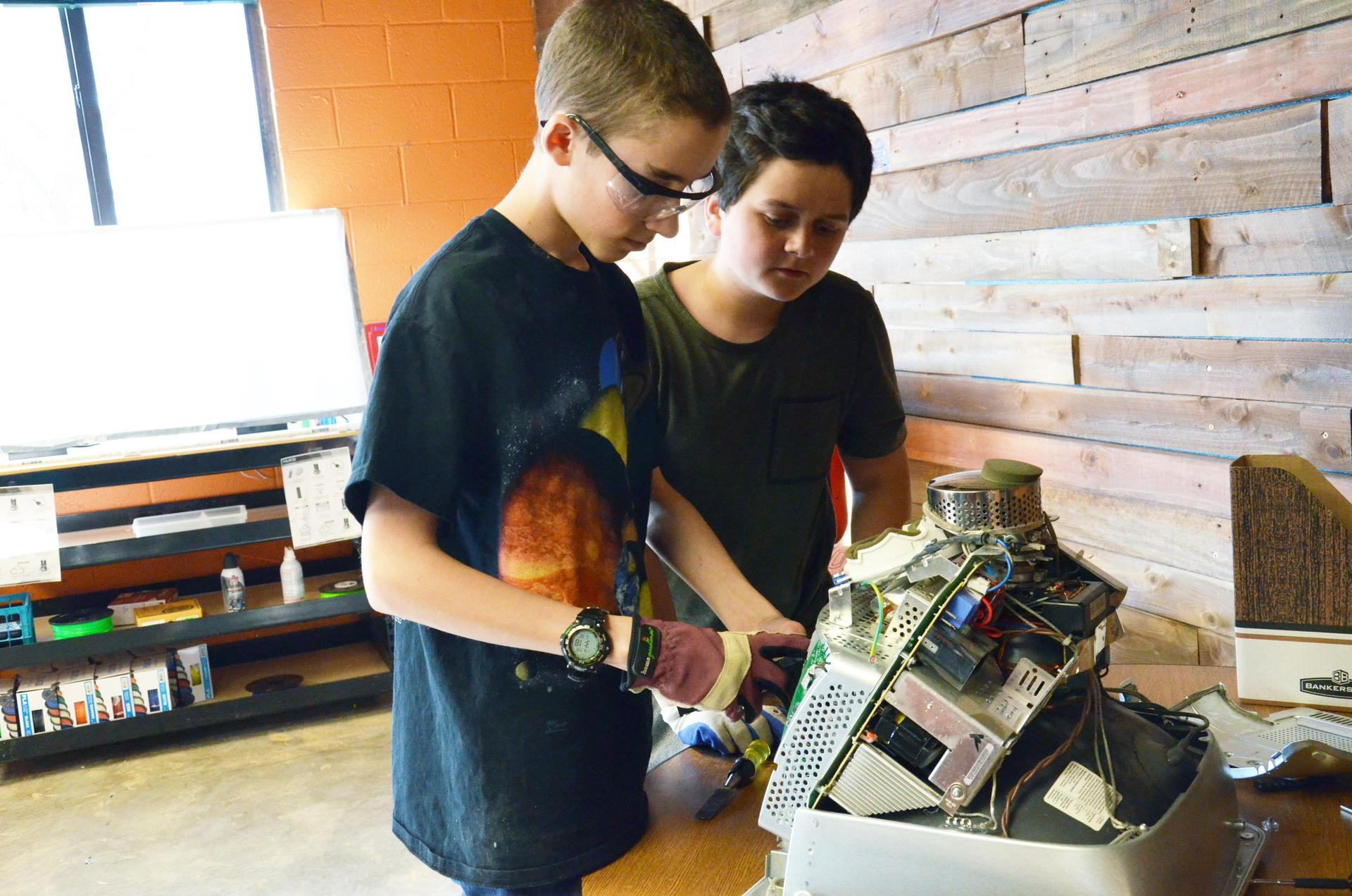 Two middle school students take apart and analyze equipment