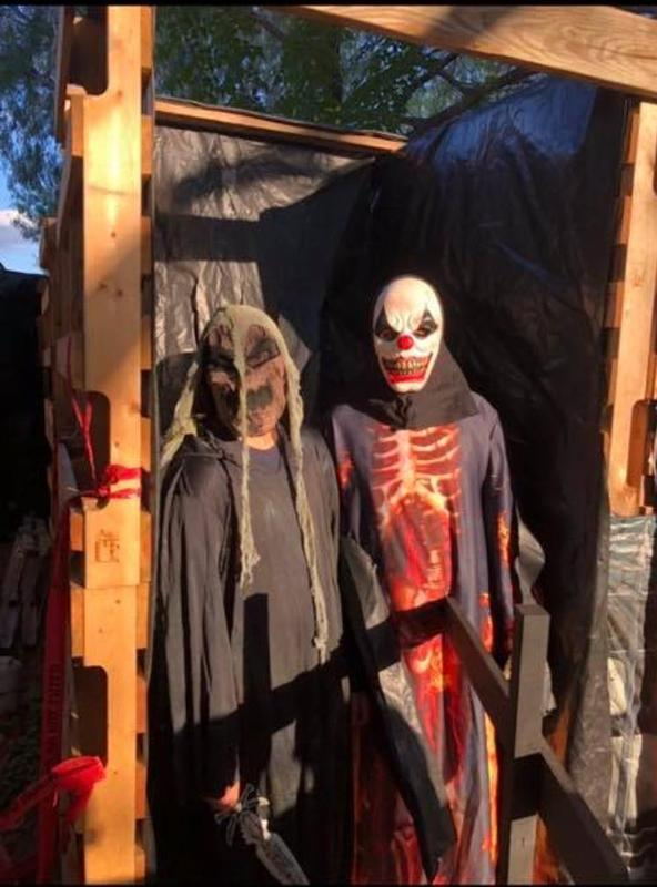 two scary figures outside haunted house.
