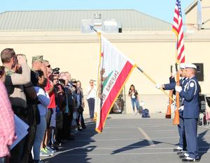 The audience reciting the Pledge of Allegiance while the JROTC cadets hold the flags.