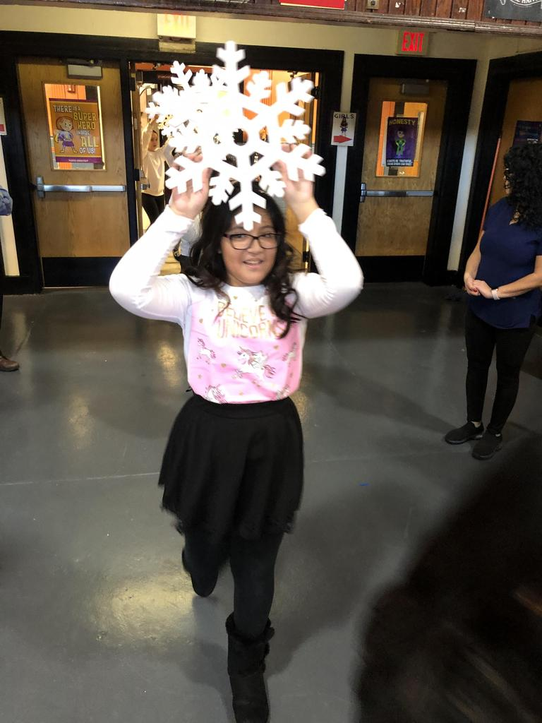 girl dressed with a pink top black leggings holding a white paper snowflake above her head entering the gym