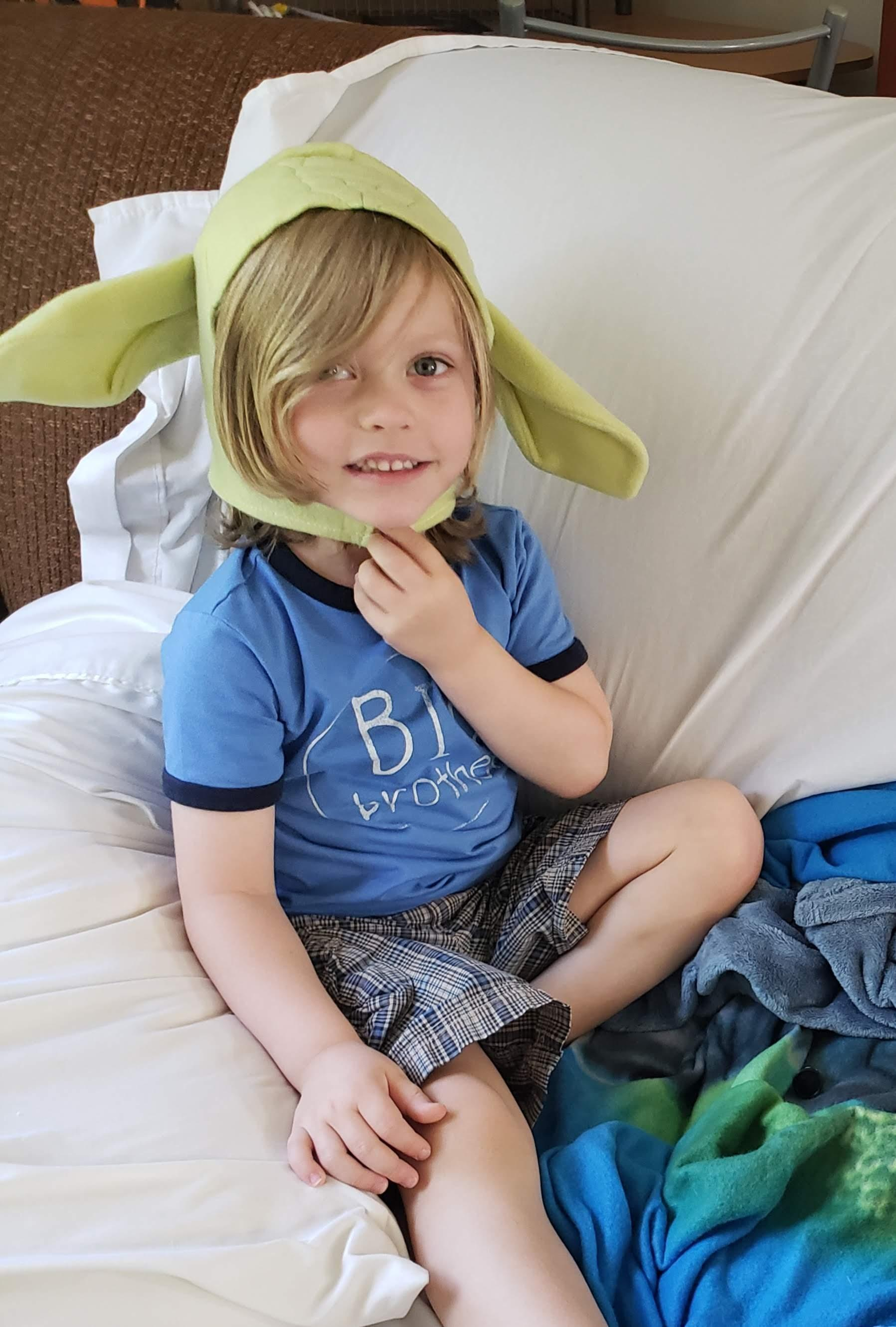 Blonde preschooler in a blue shirt wears a green Yoda ears hat while smiling and sitting on a couch