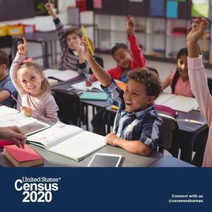 students at desks raising their hands